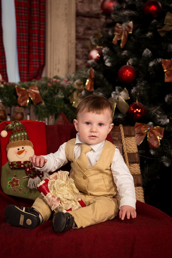Boy sitting next to a Christmas tree